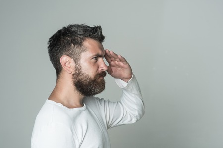 Barber fashion and beauty. Feeling and emotions. Guy or bearded man on grey background hold hand at head. Man with long beard and mustache. Hipster with serious face. Zdjęcie Seryjne