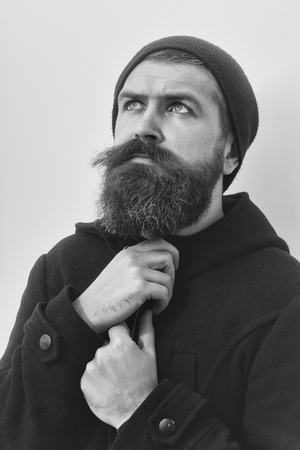 bearded man, long beard, brutal caucasian hipster with moustache on serious face, unshaven guy getting haircut by hairdresser at barbershop in black jacket, hat look up on white background