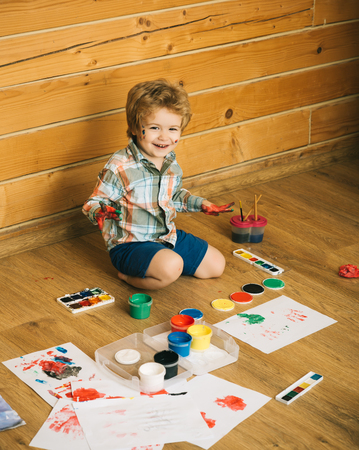 Imagination, creativity and freedom concept. Child happy smiling with colored hands, gouache paints and drawings. Kid learning and playing. Boy painter painting on wooden floor. Arts and crafts.