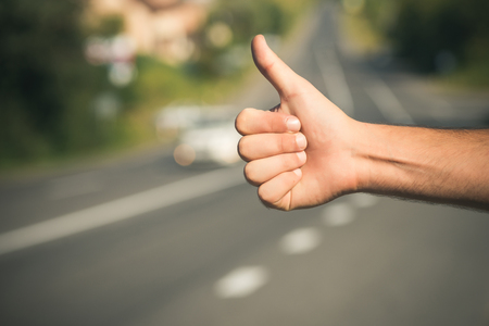 Hitchhiking, hitching, thumbing, auto stop concept. Thumbs up male hand gesture outdoors. Hitchhiker sign on road. Travel, trip, vacation, wanderlust.