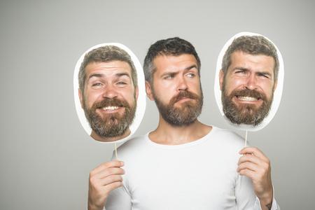 深刻な、幸せで怖い顔とヒップスターは、肖像銘板を保持します。灰色の背景に男やひげを生やした男。床屋のファッションと美しさ。長いひげと 写真素材