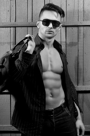Sexy serious sensual muscular young macho man with bare torso and stylish hair in shirt sun glasses and bag standing indoor on wooden background, vertical picture 版權商用圖片
