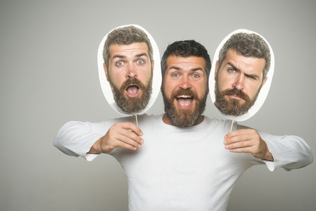Man with long beard and mustache. Guy or bearded man on grey background. Barber fashion and beauty. Hipster with happy, sad and surprised face hold portrait nameplate. Feeling and emotions. Banco de Imagens