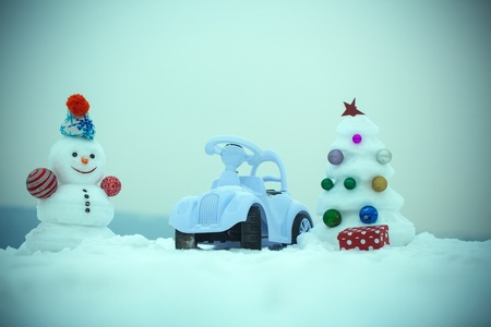 smiley face car: Christmas tree and present box on blue sky. xmas and new year. Holidays celebration concept. Snowman and toy car on snowy background. Snow sculpture with smiley face on winter day.