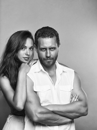 Couple of handsome bearded man in white shirt and sexy woman in pink blouse that rested on his shoulder on gray studio background Stock Photo