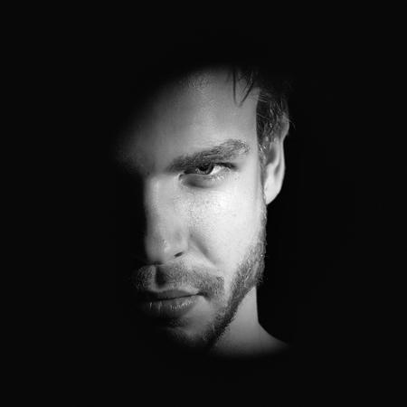 Portrait de vue agrandi d'un bel homme jeune macho barbu avec regard fort yeux noisette et lèvres sexy debout dans la lumière avec impatience en studio sur fond noir, photo carré Banque d'images - 88977765