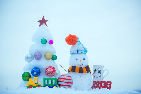 Christmas tree with decorations, toy train, cup and present box. xmas and new year. Winter holidays concept. Snow sculptures on blue background. Snowman with smiley face in hat and scarf, copy space
