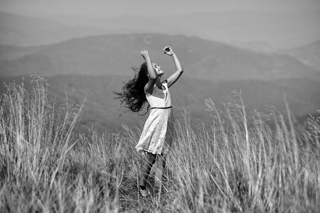 Piccola ragazza castana felice attraente in vestito da estate di pizzo bianco in piedi in valle di montagna con il giorno isounny di capelli htouching di erba secca spikelet profonda all'aperto su sfondo blu naturale, immagine orizzontale Archivio Fotografico - 89581572