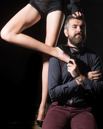 Jongen aan tafel met vrouwelijke benen. Mens in overhemd op zwarte achtergrond, matriarchie wordt geïsoleerd die. Liefde en relaties, domineren. Benen van vrouw in schoenen bij de mens met baard. Romantiek en verliefd.