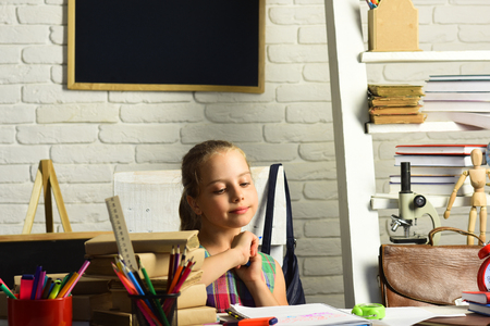 Kid with colorful stationery on white wall background. Girl with thoughtful face expression does homework. Pupil with books and school supplies. Childhood and back to school concept.
