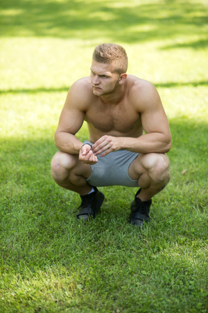 Man sit on green grass on sunny day. Sportsman with muscular torso on natural landscape. Macho with six pack, ab, biceps, triceps in shorts. Fitness, sport, training concept. Summer vacation, health. Stock Photo
