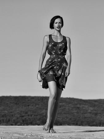 Het mooie donkerbruine slanke model van de meisjes jonge mooie vrouw met naakte voeten in sexy blauwe kleding stelt op hemelachtergrond