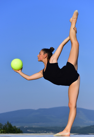 Gymnastic school and energy. Woman gymnast in black sportswear with green ball in split. Flexibility in acrobatics and fitness health. Workout of girl on blue sky background. Sport and success.