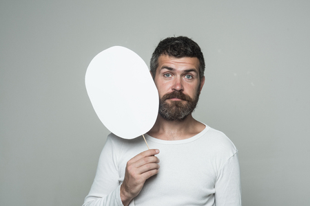 Hipster with sad face hold paper nameplate. Guy or bearded man on grey background. Barber fashion and beauty. Feeling and emotions. Man with long beard and mustache., copy space