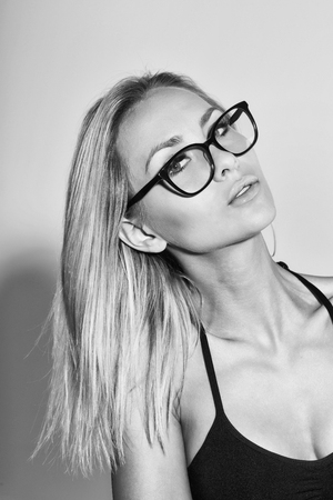Pretty student girl or teacher woman in cute stylish eyeglasses with long blond hair wearing black bra, top on grey background. Education concept Stock Photo