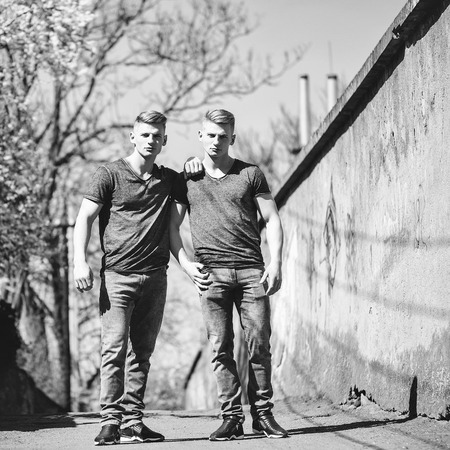 identical: Twin brothers young handsome friendly blond men in jeans pose with serious look outdoor on streetscape background