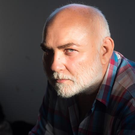 格子縞のシャツに白髪ひげと大胆な頭部額の年配の男性が座っています。高齢化、成熟、退職の概念。