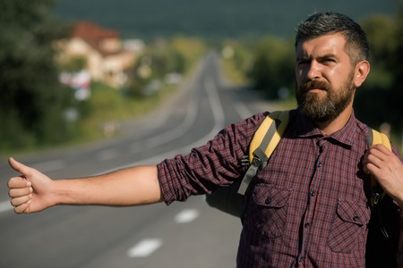 Tourist traveler travel auto stop. Summer vacation concept. Adventure, discovery, wanderlust. Man with backpack hitchhiking on road. Hipster hiker show thumbs up hand gesture on sunny day. Stock Photo