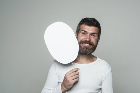 Man with long beard and mustache. Guy or bearded man on grey background. Barber fashion and beauty. Feeling and emotions. Hipster with happy face hold paper nameplate., copy space