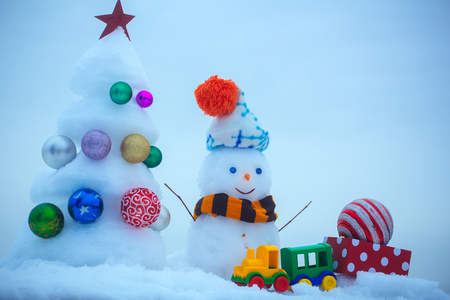 Snowman with smiley face in hat and scarf. Snow sculptures on blue background. xmas and new year. Christmas tree with ball decorations, toy train and present box. Winter holidays concept. Stock Photo