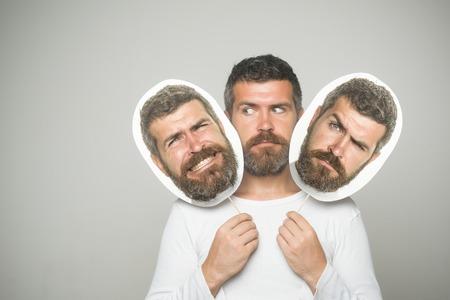 Gevoel en emoties. Man met lange baard en snor. Man of bebaarde man op grijze achtergrond. Hipster met droevig gezicht houdt portretnaambord. Kapper mode en schoonheid.
