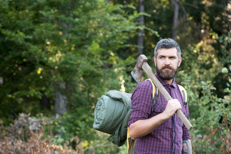 Man lumberjack with bearded face hold backpack and axe on shoulder on summer day on natural landscape. Logging and chopping concept.
