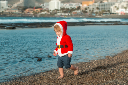 Cute baby boy in red santa coat with hood and shorts walks barefoot on grey pebble beach by blue sea on sunny summer day on natural background Stock Photo
