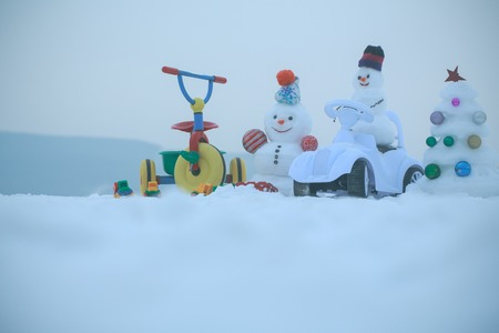 Tricycle and toy car on snowy background. Snowmen and snow xmas tree on white sky. Winter holidays celebration concept. Festive surprise and presents. Christmas and new year.