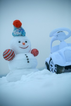 Snowman and toy car on winter day on grey sky on snow background. Christmas and new year. Holidays celebration concept Stock Photo