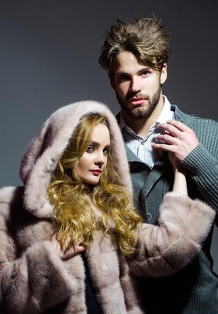 visone: Boyfriend hold hand of girlfriend in mink fur coat, hood on grey background. Fashion, style, winter clothing concept