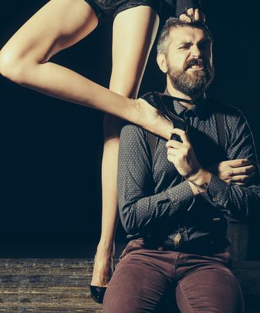 Mens in overhemd op zwarte achtergrond, matriarchie wordt geïsoleerd die. Benen van vrouw in schoenen bij de mens met baard. Romantiek en verliefd. Liefde en relaties, domineren. Jongen aan tafel met vrouwelijke benen.