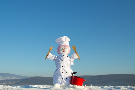 Winter party and cooking. Happy holiday and celebration. Christmas or xmas decoration. New year snowman chef from snow with pot. Snowman cook with wooden spoon and fork.