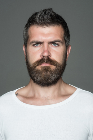Man with long beard and mustache. Hipster with serious face. Feeling and emotions. Guy or bearded man on grey background. Barber fashion and beauty.