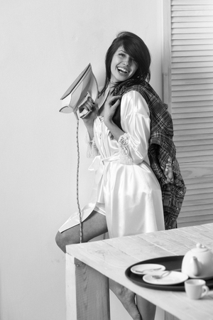 Happy pretty girl or cute woman, housewife, with long brunette hair in sexy dressing gown smiling with electric iron in hand for ironing clothes in kitchen on white wall. Housework and housekeeping Stock Photo