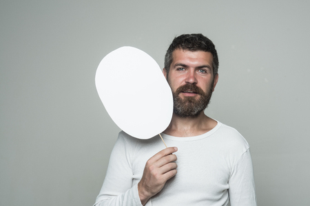 Man with long beard and mustache. Guy or bearded man on grey background. Barber fashion and beauty. Feeling and emotions. Hipster with smiling face hold paper nameplate., copy space