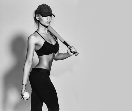 Pretty girl, sporty woman player, fit athlete, with sexy, muscular body, torso, hold green baseball bat, ball in black sportswear, bra, cap on grey background. sport and healthy lifestyle, copy space Stock Photo