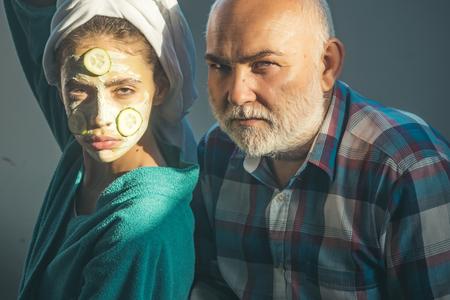 少女と老人のひげと大胆な額。女性の顔にキュウリ マスクと頭の上のタオル。若さ、美しさ、新鮮さ、活性化、崩壊、高齢化時代のコンセプト。