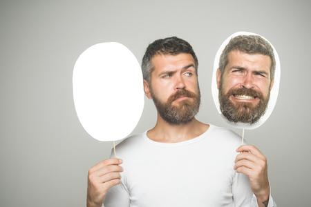 Hipster met droevig gezicht houdt het naamplaatje van het portret. Kerel of de gebaarde mens op grijze achtergrond. Man met lange baard en snor. Gevoel en emoties. Kapper mode en schoonheid., Kopieer de ruimte