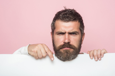 Barber fashion and beauty marketing. Man with long beard and mustache. Feeling and emotions. Hipster with sad face hold paper. Guy or bearded man on pink background.