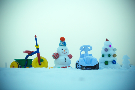 Snowman and snow xmas tree on blue sky. Winter holidays celebration concept. Tricycle and toy car on snowy background. Festive surprise and presents. Christmas and new year.