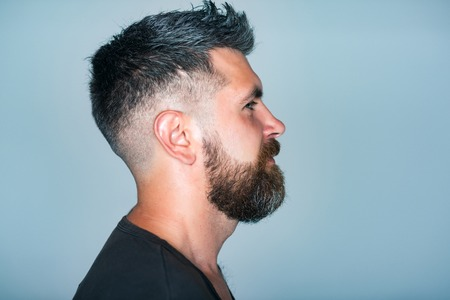 Hipster with bearded face profile and stylish hair pose on blue background. Barber, barbershop, hairdresser or beauty salon concept, copy space