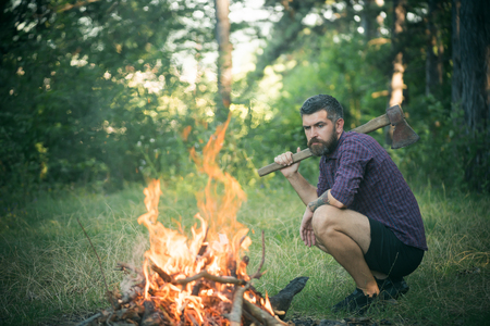 Man lumberjack with axe look at bonfire flame on summer day on natural landscape. Traveling, camping, hiking, vacation concept Фото со стока