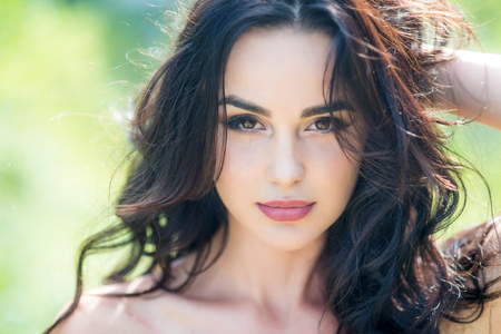 Girl with long brunette hair on sunny day. Woman face with makeup on young skin in nature. Skincare, youth, health concept. Fashion, beauty, visage. Standard-Bild