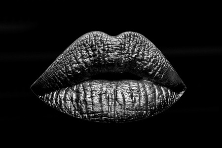sexy female golden or gold lips isolated on black background as makeup or body art painted mouth metallized color with violet contour