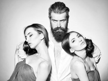 Bearded handsome man in white shirt with two young pretty women in violet dresses with long hair in studio on grey background