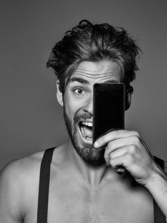 Excited handsome man fashion sexy young blond bearded male model with suspenders on topless sexi nude torso hides face behind smartphone or mobile phone on grey background Banco de Imagens