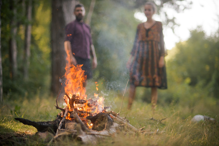 Man and woman on blurred background look at fire flame in wood. Hiking, camping, lifestyle concept.