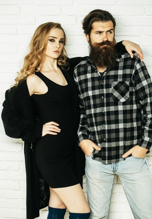 Couple in love on white brick wall. Woman in black dress, coat hug man in plaid shirt. Girl with long blond hair and bearded hipster. Fashion, clothing, style concept