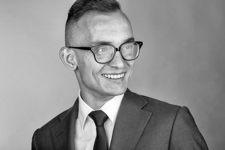 Young fashion businessman with nerd glasses on smiling face and stylish hairdo in jacket with tie on studio background