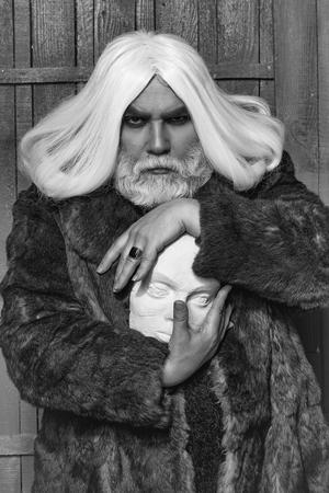木製の背景にリングと手に白い彫刻の頭を保持毛皮のコートで長いひげを生やした古いドルイドの髭の男